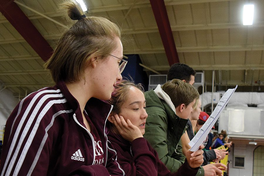 O CAPTAIN, MY CAPTAIN. Franzi Wild, left, looks over a heat sheet with co-captain Hannah Herrera at the first Midway Miles meet Feb. 23. While injured and unable to run for part of the indoor track season, Franzi has made an effort to stay intertwined in the team's athletic and social aspects.