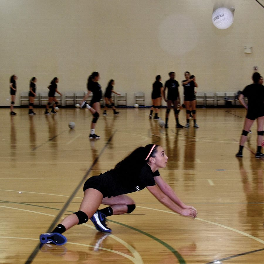 PRACTICING FOR PERFECTION. Lunging toward the ball, sophomore Sydney Rogers practices at Chicago Elite in February. Sydney practices over 15 hours each week.