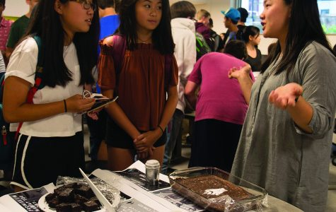 EXTRACURRICULAR EXCESS. Freshmen Eliza Doss and Iris Xie listen to senior Elizabeth Van Ha talk about Social Justice Committee at the annual club shopping event, where approximately 60 clubs set up in Café Lab Sept. 20 during lunch to attract new members.