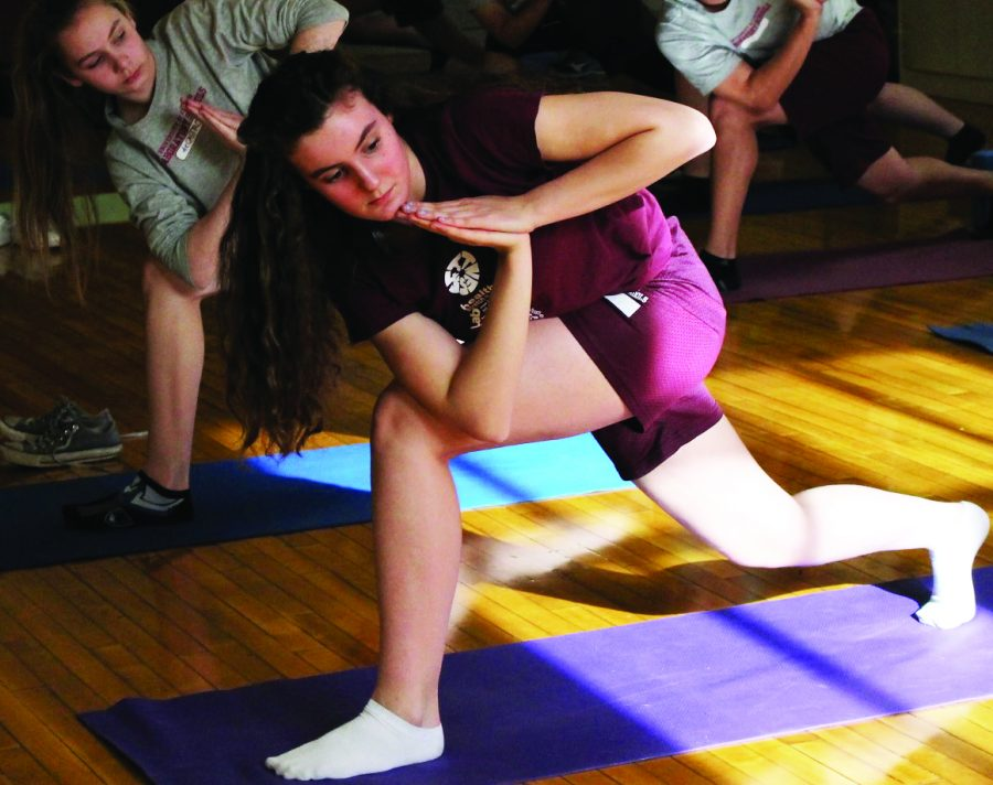 GETTING CENTERED. Freshmen Lea Rebollo Baum does yoga with her classmates in Ms. Greene's yoga and pilates class.