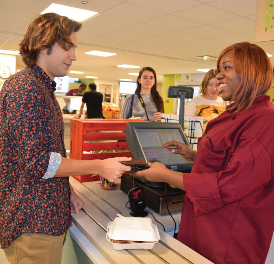 PASS THE WALLET. Cashier Cassandra Judkins, at right, smiles as she passes senior Tomás Linquist his wallet and a few kind words. Students and cafeteria workers have close relationships, checking in throughout the day.