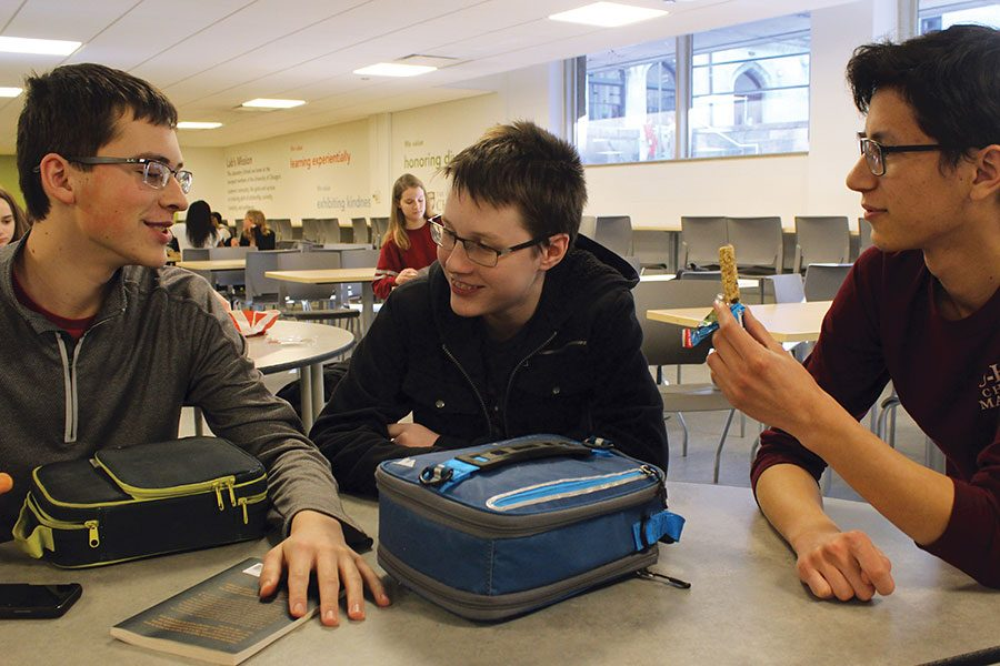 ENJOYING COMMUNITY. Juniors Ben Epley, Derek de Jong and Abraham Zelchenko talk at a cafeteria table during lunch. Ben came to Lab as a freshman, Derek  in fourth grade and Abraham in Nursery 3. Their different  lengths of time at Lab haven't affected the strength of their friendships.