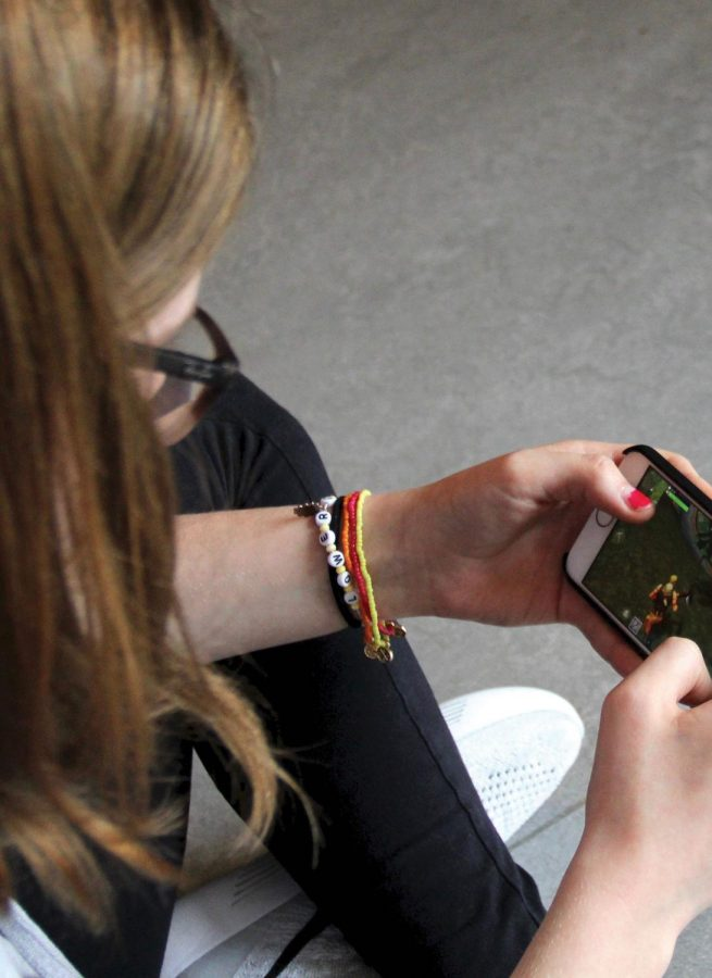 """HALLWAY GAMING. Beginning her game of """"Fortnite Battle Royale"""" by gliding down to the surface, junior Aly Latherow plays in the junior hallway during open time May 22. Players were able to register for """"Fortnite"""" on iOS beginning March 12."""