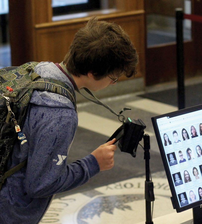 TAPPING IN. A middle school student taps his ID as he enters school in the morning. Lab's new security policy requires students to always carry their IDs and lanyards. The ID photos, once scanned, show up on the security guard's screen.