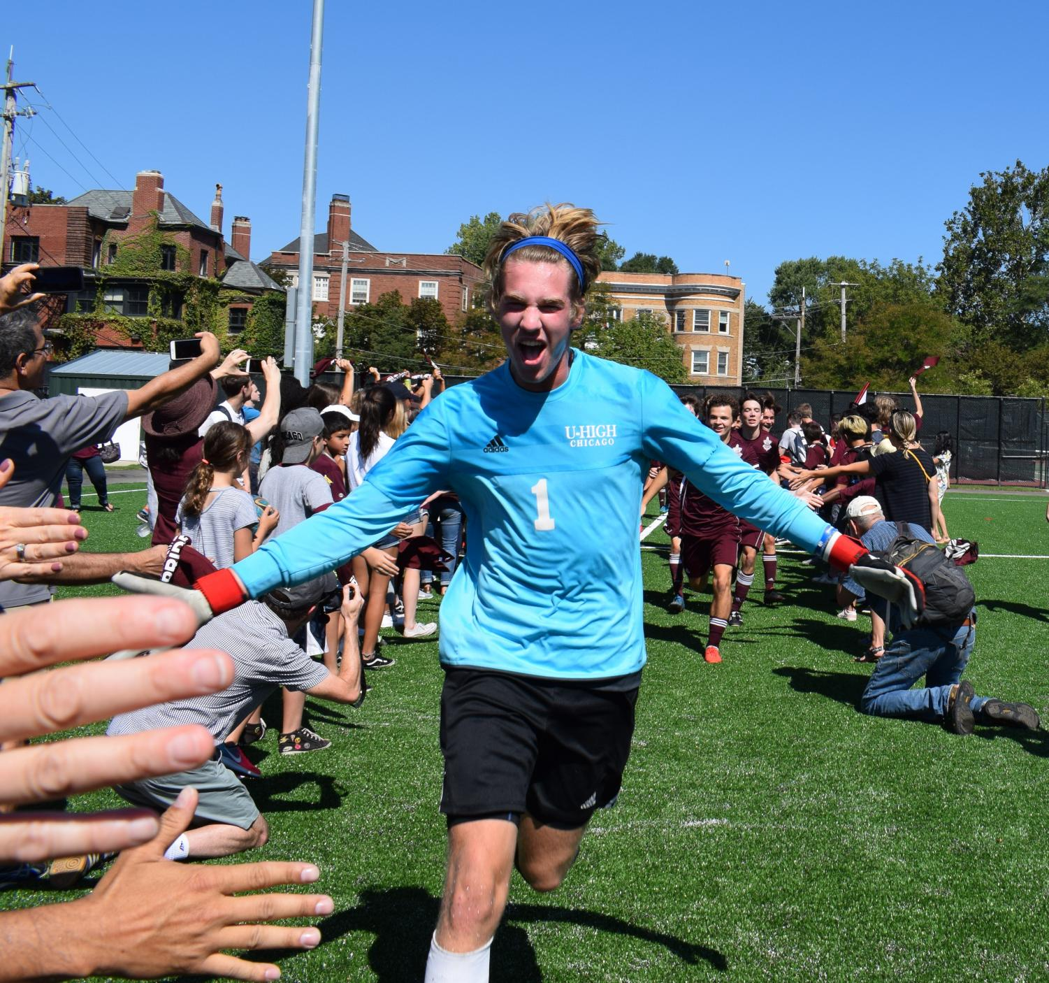 U-High Varsity Goalie Jamie Miller gives fans high fives as he leads the team onto the field.