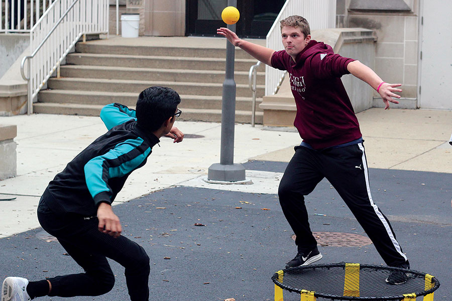 SPIKE IT. Winding up to hit the ball, Zach Leslie plays Spikeball with Gaurav Shekhawat on Kenwood mall during lunch. Spikeball has been described as a cross between four square and volleyball. The boys said they use it as a way to bring friends together and stay active while not playing soccer.