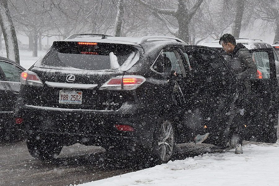 Sophomore Jaden Li steps out of his car Nov. 26. The first snowfall of the year has slowed travel times.