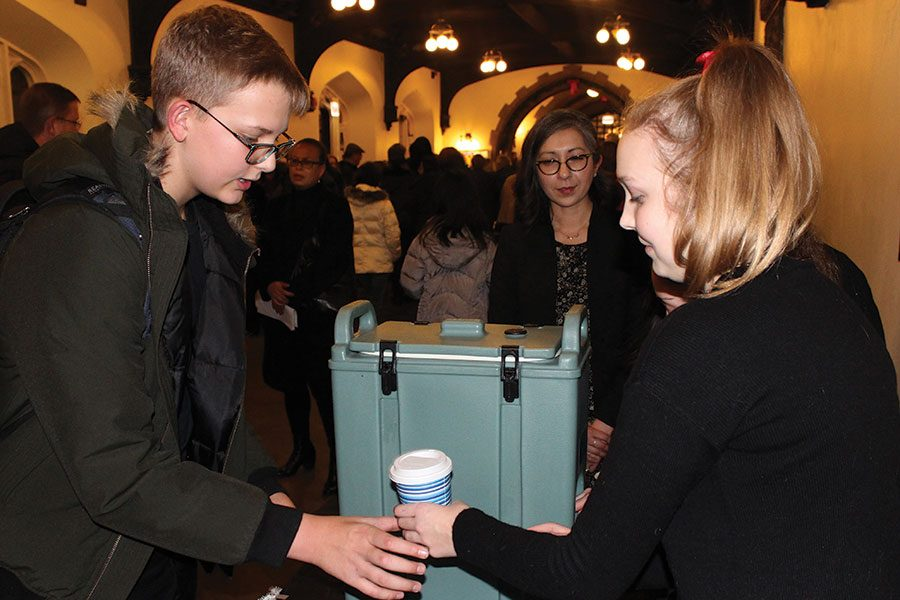 COLLECTING CONTRIBUTIONS. Orchestra member Victoria Welch hands freshman Brandon Bousquette a hot chocolate after the U-High music concert Dec. 6. The orchestra performed along- side the band and sold drinks help Puerto Rico with hurricane relief.