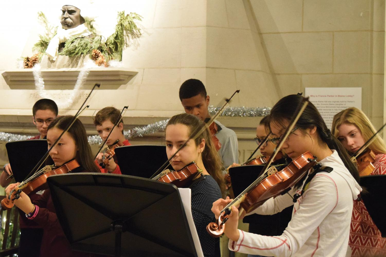SOUND OF STRINGS. U-High Orchestra plays Christmas and Hanukkah music for lower school students in Blaine Lobby. The Lobby String is a play on Lab's traditional Lobby Sings, at which students gather in a lobby and sing together.