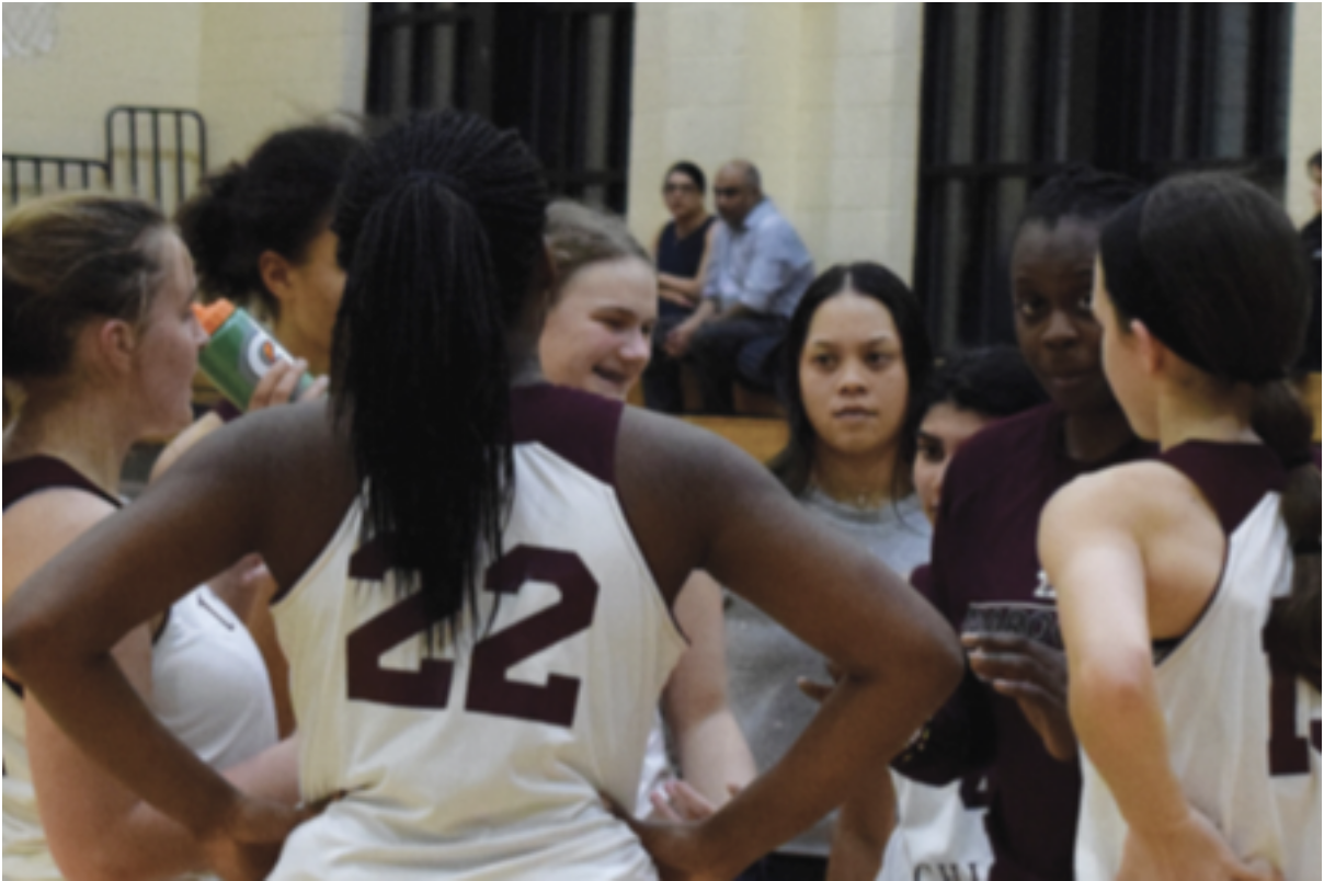 PASS IT ON. Girls basketball players huddle up and motivate each other before the fourth quarter of home game, Jan. 15. Down by 20 points, the team was not discouraged as their coach passed along positive energy and support. U-High finished the game at 41-48.