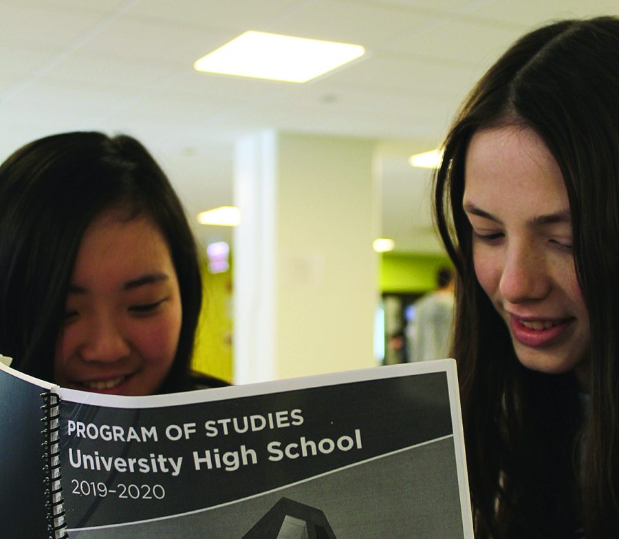 SELECTING+STUDIES.+Emily+Chang+and+Isabel+Randall+look+over+the+2019-20+Program+of+Studies.+Students+have+the+opportunity+to+choose+a+few+new+semester-long+courses.