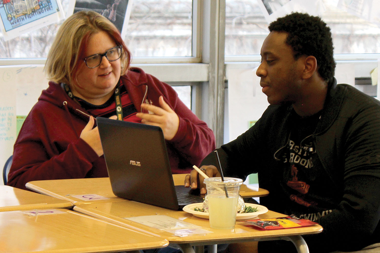 BUILDING COMMUNITY. Gesturing, middle school language teacher Deb Foote discusses with senior Robert Coats during a Spectrum meeting. Ms. Foote is the new adviser, taking over former teacher Daniel Bobo-Jones' position.