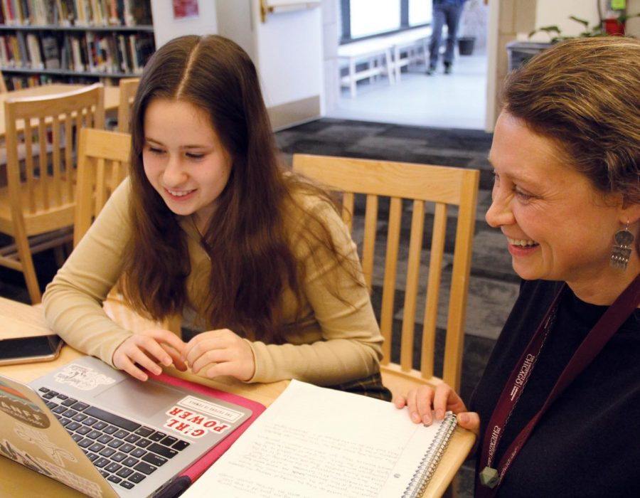 HELPING STUDY. Librarian Susan Augustine helps junior Annie Billings with an assignment of hers. The librarians are often available to help students with their work, including conducting research for classes about what books are needed for certain projects.