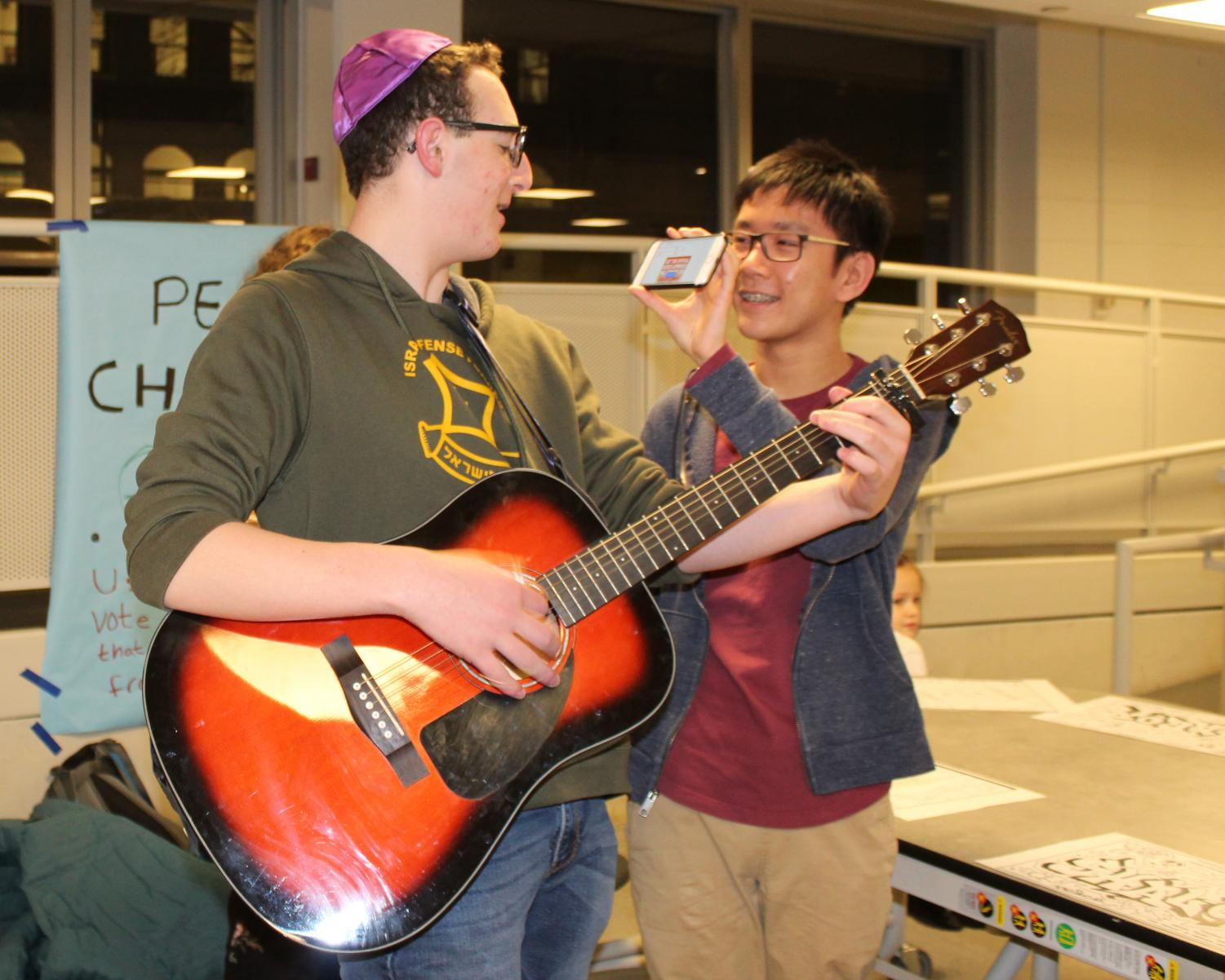 "SHABBAT SONG. Jeremy Ng, right, shows Nathan Appelbaum the guitar score for a Coldplay song at the first-ever all-school Shabbat dinner potluck in Café Lab on the evening of Jan. 25. The potluck, which was hosted by the U-High Jewish Students' Association and the Lab Jewish Affinity Group, brought the Jewish community together. ""We made it a goal to educate and celebrate Shabbat, Judaism, and community, and in just two hours, we achieved that and more,"" Nathan said."