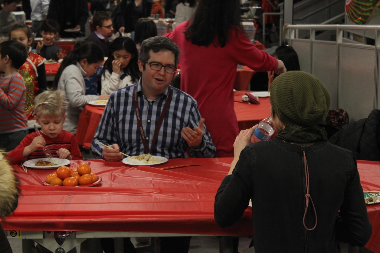 Colin Rennert-May, English teacher, talks to Sunny Neater, art teacher, during the Lunar New Year Dinner Feb. 7.