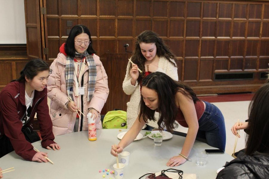 Lea Rebollo Baum and Alexis Chia complete a chopstick ice-breaking activity prepared by the visiting Chinese students.