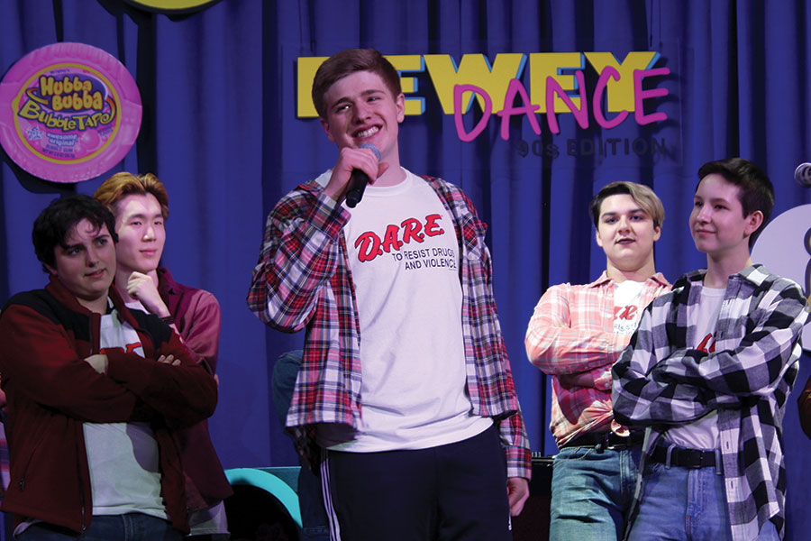 """NINETIES NIGHT. Miles Warshauer belts out his solo on """"The Fresh Prince of Bel Air,"""" as fellow Bel Canto members Luca Carroll-Maestripieri, Tommy Hsee, Nicki Sekhar and Jonah Schloerb, look on at the Dewey Dance, March 9. Bel Canto was one of several student performances at the event."""