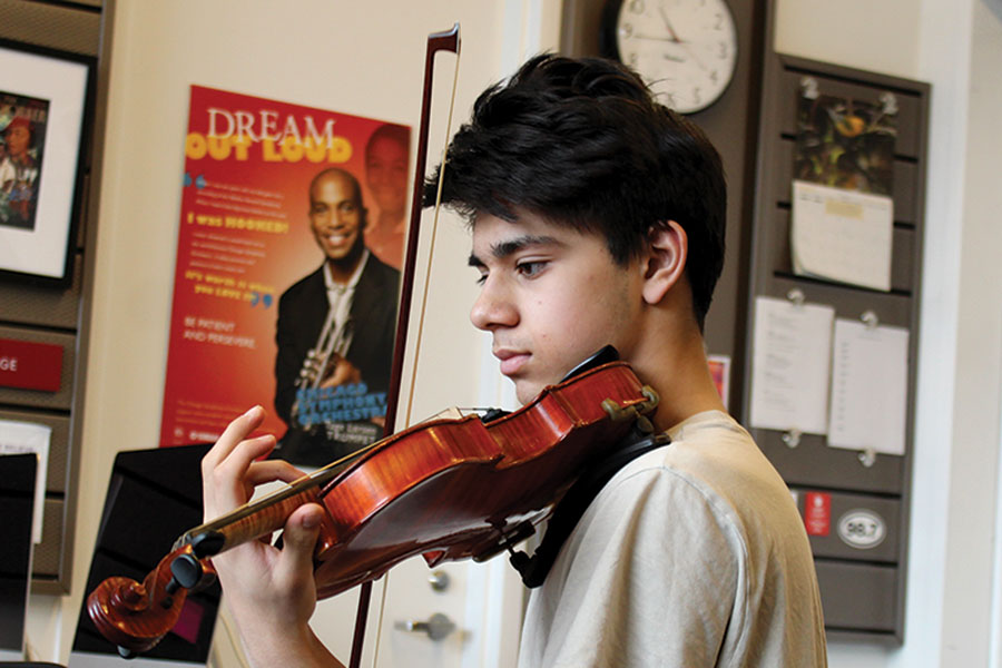 GIVING BACK. Eyes on his music, sophomore Rohan Shah practices with Chamber Collective. With the guidance of orchestra teacher Rozalyn Torto, he is currently organizing performances at hospitals and retirement homes. Rohan hopes to move and inspire his audience with each performance.