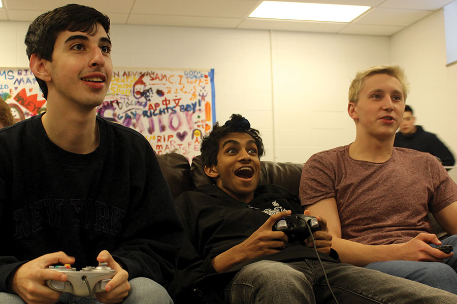"GAME FACES. Seniors Bassem Noghnogh, Shiva Menta and Mitch Walker play ""Super Smash Bros."" in the Senior Lounge on the communal TV."