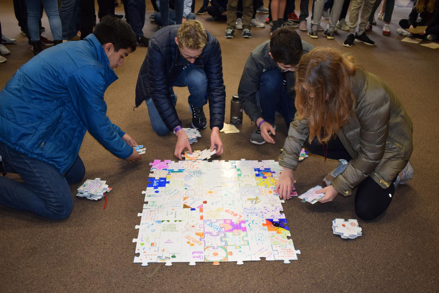 Junior Class vice president Suleyman Ahmed, Junior Class president Ben Cifu and Cultural Union representatives Kepler Boonstra and Ava Kucera disassemble a puzzle that was created by the junior class. Each individual student added a single puzzle piece describing what they brought to the grade, which was the culminating activity at junior retreat from April 9-11 at Camp Lake, Wisconsin. Juniors worked on various activities intended to foster bonds and give students a new perspective on their classmates.