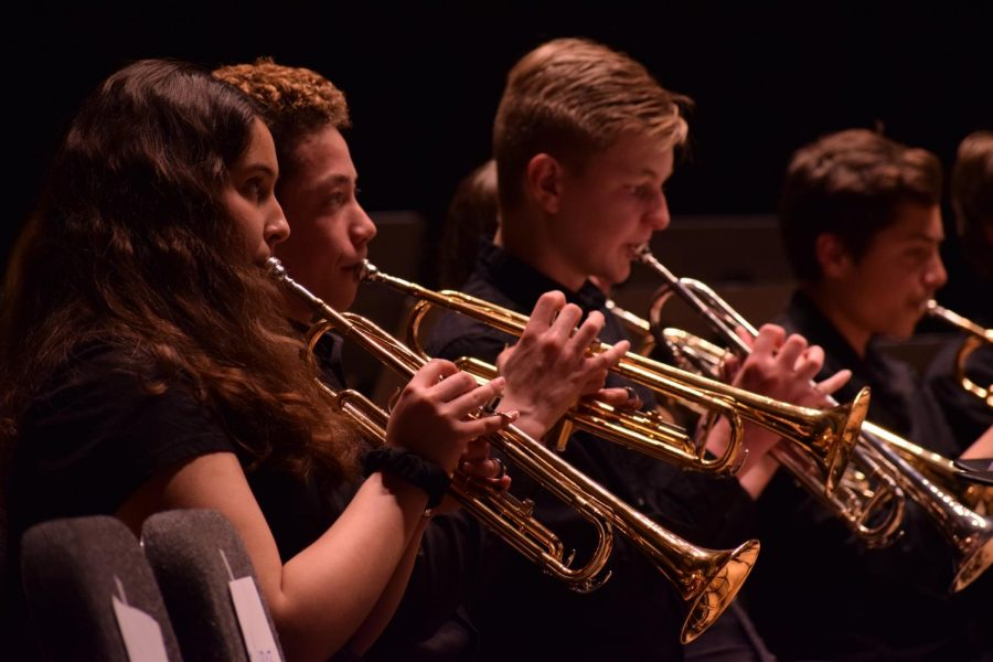 BAND-ING+TOGETHER.+Freshmen+Amelia+Scharma%2C+Will+Trone+and+Benjamin+Stankiewicz+play+their+trumpets+at+the+seventh+through+12th+grade+band+concert+at+Mandel+Hall+April+23.+Their+performance+included+pieces+such+as+%22The+Witch+and+the+Saint%22+and+%22Air+for+Band.%22