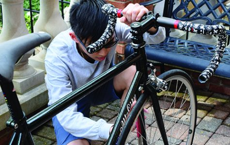 BUILD IT, RIDE IT, LOVE IT. Junior Aden Chon kneels down to tighten the axle nuts on the front wheel of his custom made bike. Aden has assembled his bike throughout the past year, first getting into it after realizing just how much money he was spending on repairs at local bike shops.