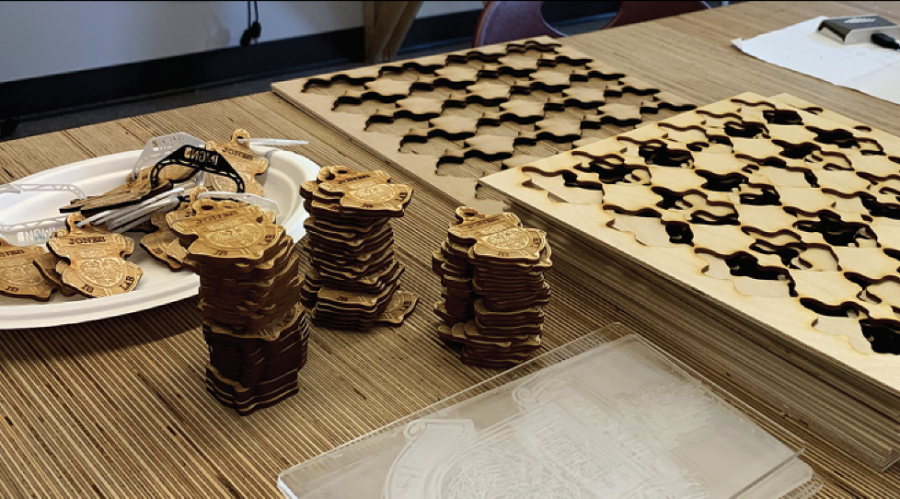 "MAKING WAVES IN THE MAKERSPACE. Stacks of carved wooden keychain acessories reading ""Jones Is Lab"" await distribution. Students have used the makerspace to laser-cut the medallions, which have been in increasing demand."