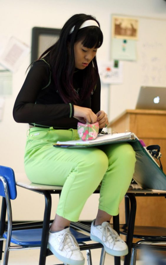WHO NEEDS A CHAIR? Sitting on a desk (but surely careful not to get her bright green pants dirty), sophomore Chloe Ma showcases her neon outfit.