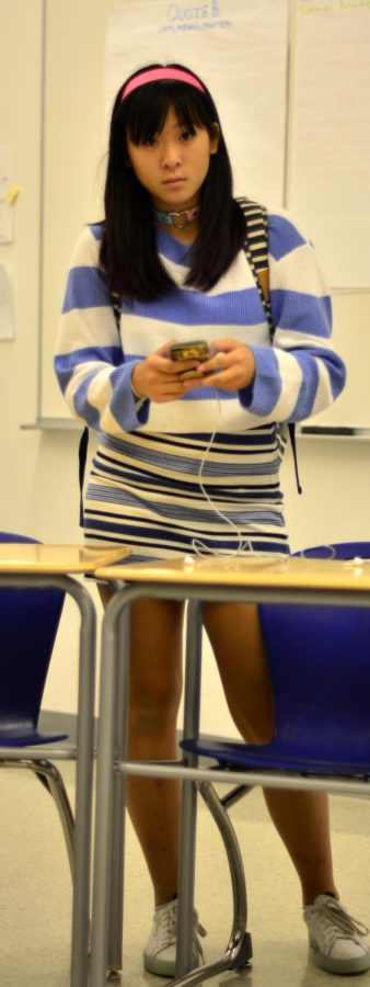 STRIPES.+Wearing+a+striped+sweater+and+skirt+%28and+backpack%29%2C+sophomore+Chloe+Ma+checks+her+phone+in+a+U-High+english+classroom.+