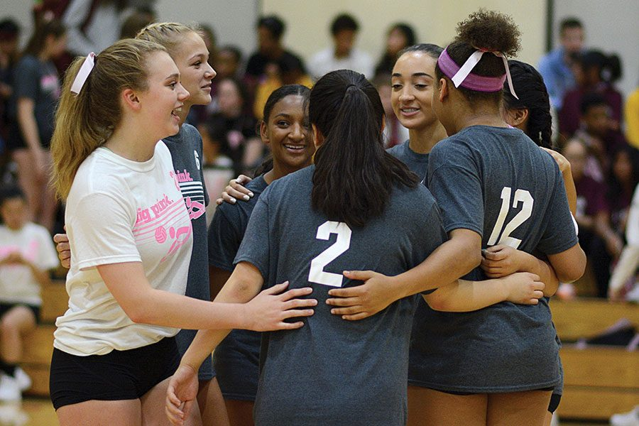 Varsity volleyball players celebrate after a play at Dig Pink fundraiser
