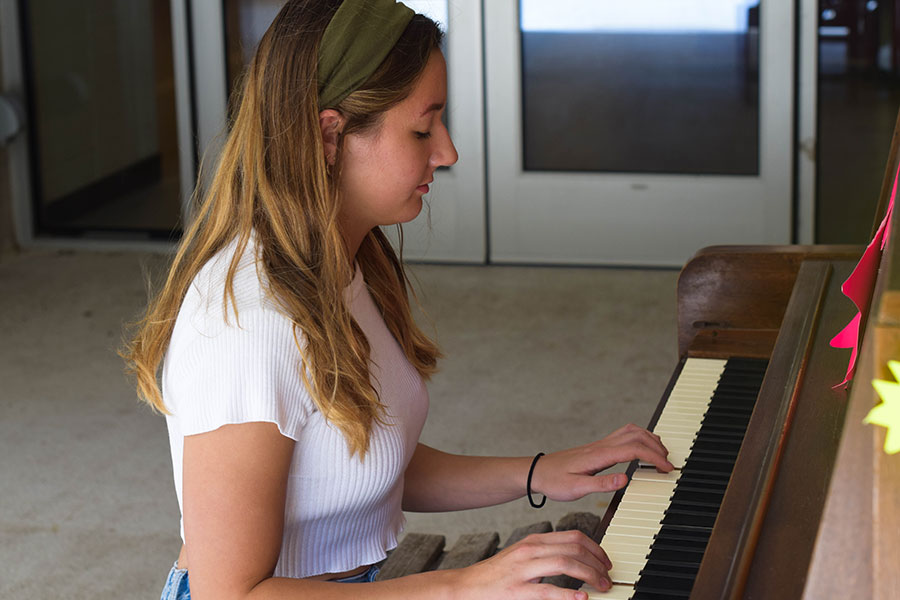 Ava McKula plays a song on the piano outside C116 near Judd Lobby.