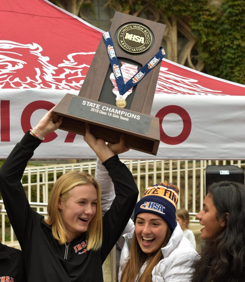 Senior girls tennis members Macy Beal, Izzy Kellermeier, and Ananya Asthana hold their state trophy high at the victory rally Oct. 28. This was the first state championship a girls team has won in U-High history.