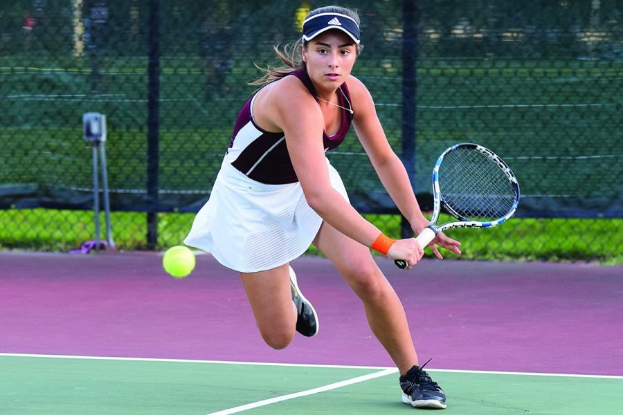 TIGHT-KNIT TENNIS TEAM. Senior Isabella Kellermeier sprints to the ball during a tennis match against Elgin Academy Sept. 17. U-High won the match 5-0. The girls tennis team is undefeated and players pride themselves in their welcoming team environment.