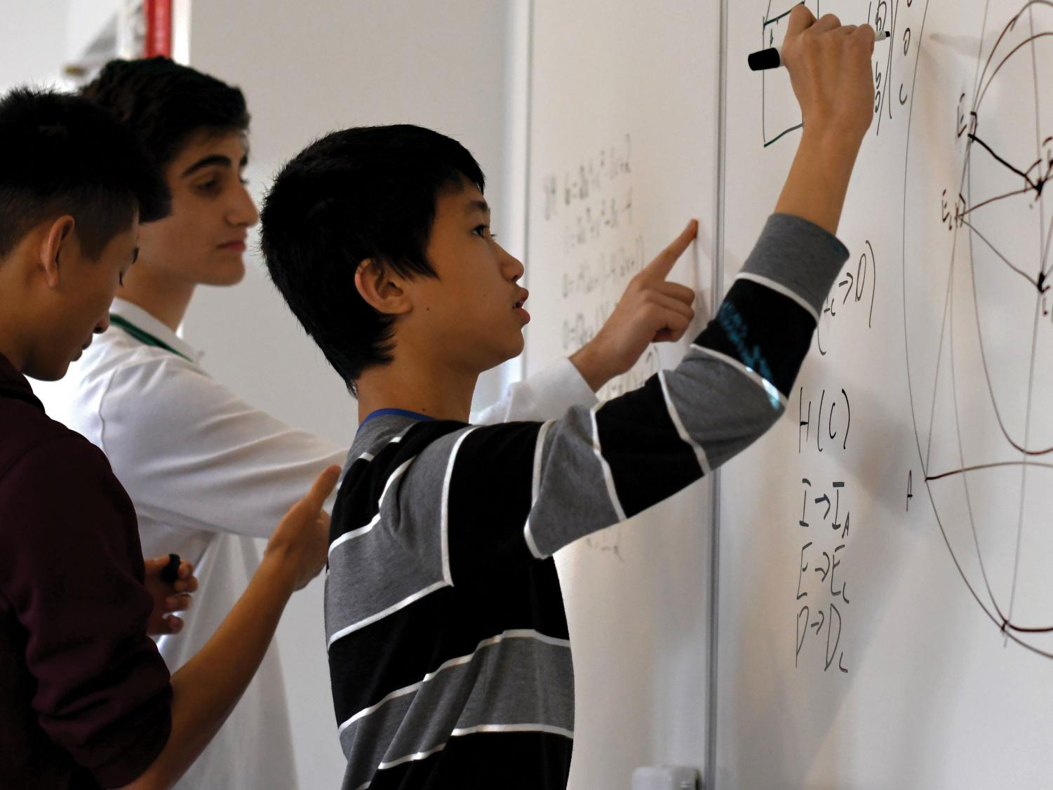 FINDING THE FORMULA: Surrounded by collaborating Mathematics team members, freshman Jeffery Chen works through questions on the white board. He said he enjoys coming up with creative solutions to difficult  locgic problems.
