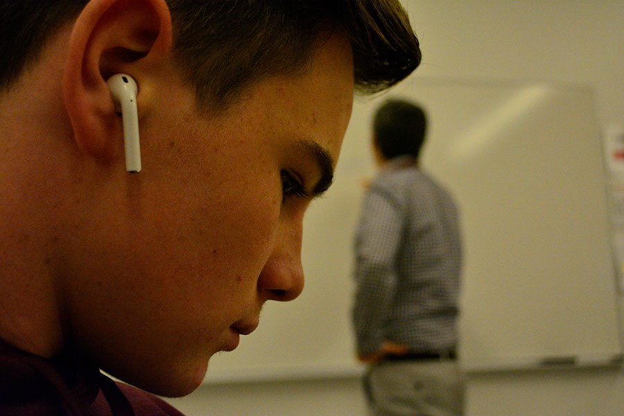 Sophomore Theodore Arado sits in English class with an Apple AirPod in one ear, his teacher Colin Rennert-May in the background. It's not uncommon to see students wearing AirPods throughout the school day.