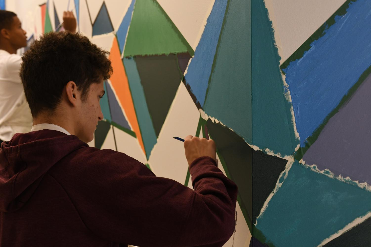 Arts students Gabriel Issa (foreground) and Brent Pennington (background) add personalized colors to hallways between Judd, the Middle School and Gordon Parks Arts Hall. The mural was inspired by the artwork of Amanda Williams, who was graduated from Lab in 1992.