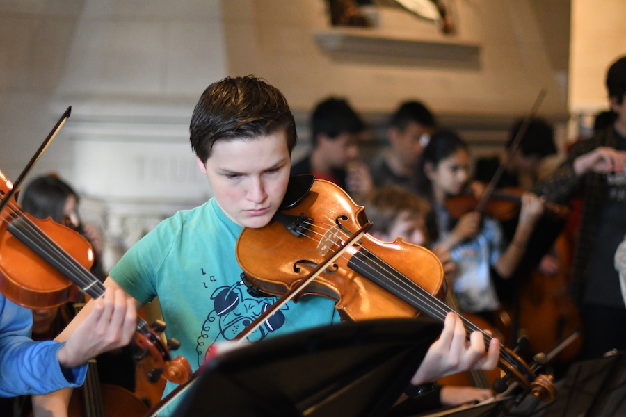 Focusing on his music, sophomore Julien Derroitte plays his viola in Blaine Lobby.