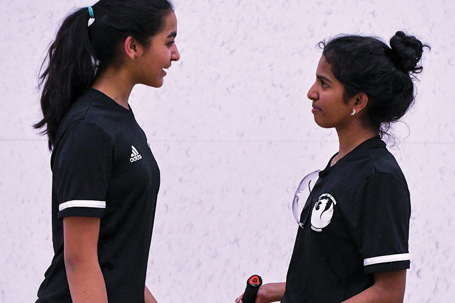 SISTERLY STRATEGY. Serena Thomas and Sara Thomas discuss a squash point. Serena and two other girls joined Sara on the squash team after Sara spent two years as the team's sole girl.
