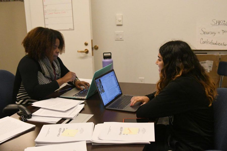 With back-to-back computers, junior Sana Shahul and her independent study supervisor, Mariah Bender, discuss the paper Sana is writing as the culmination of her study of Indian immigration into Tanzania