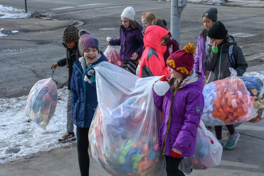 Bundled up, the students of Stephanie Mitzenmacher's fifth grade class stroll excitedly down 59th Street, carrying bags of many-colored paper chains. The class connected a chain between Blaine Hall and Earl Shapiro Hall, working with their kindergarten buddies in Delores Rita and Deb Del Campo's class.