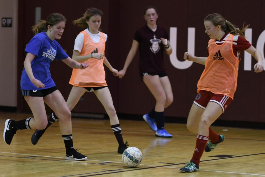 KICKIN' IT. Running to the ball, Eleanor Skish, Sarah Brady and Zoe Stephens fight for the ball during a futsal game. During the  season, two teams made up of five players a side play intrasquad games to develop skills and a closer team community. In accordance with IHSA rules, the winter program does not include any formal coaching and is both student-led and optional for team members.