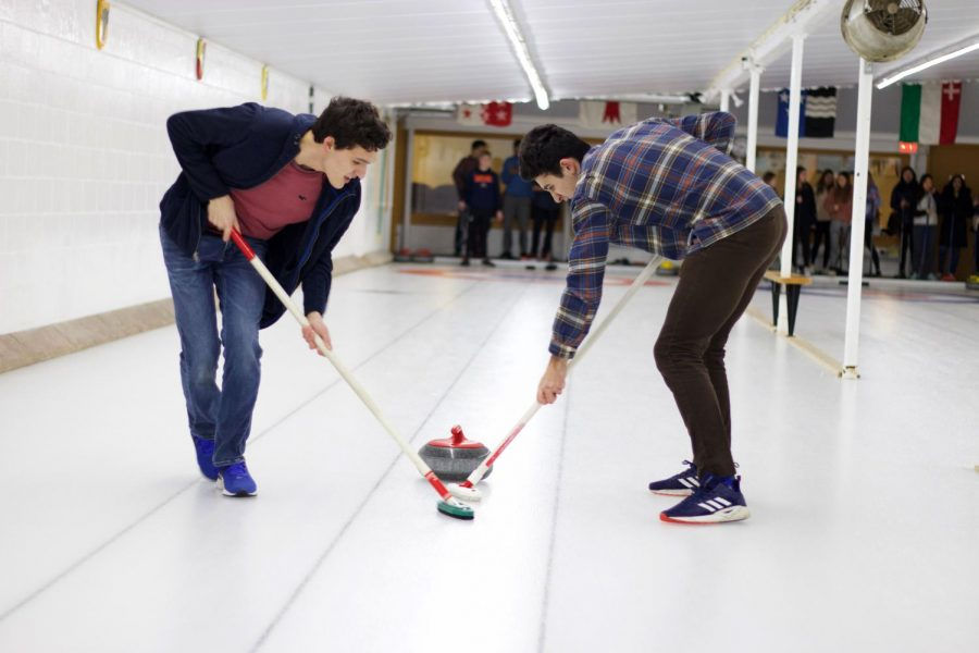 CURLING COMMUNITY. Seniors Max Polite and David Libes sweep the ice at the Alpine Curling Club in Monroe, Wisconsin during senior retreat Feb. 11. Over the next two days, seniors chose two to three activities from curling, downhill skiing, sledding, ice skating, hiking, bowling, attending a YWCA recreational facility and shopping in Galena. Additionally, there were large group activities, including an advisory-based trivia competition on the first night and inflatable arenas on the second. Unexpected weather on the last day postponed the return trip, causing some seniors to be delayed more than two hours.