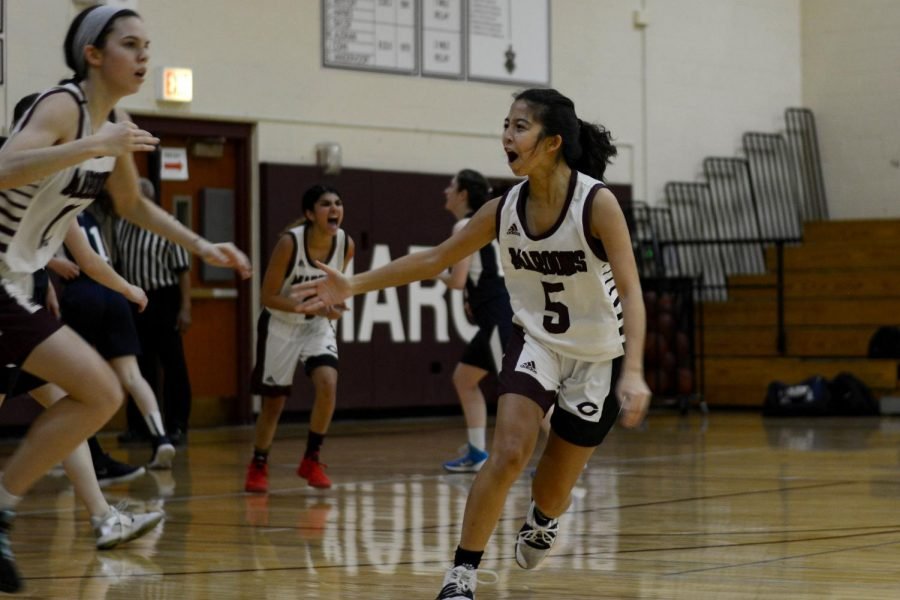 Meena Lee, right, participant in the 2020 IHSA Three-Point Showdown, celebrates with her teammates during a home game against Latin. Meena advanced to the preliminary level of the state tournament in Normal, IL.