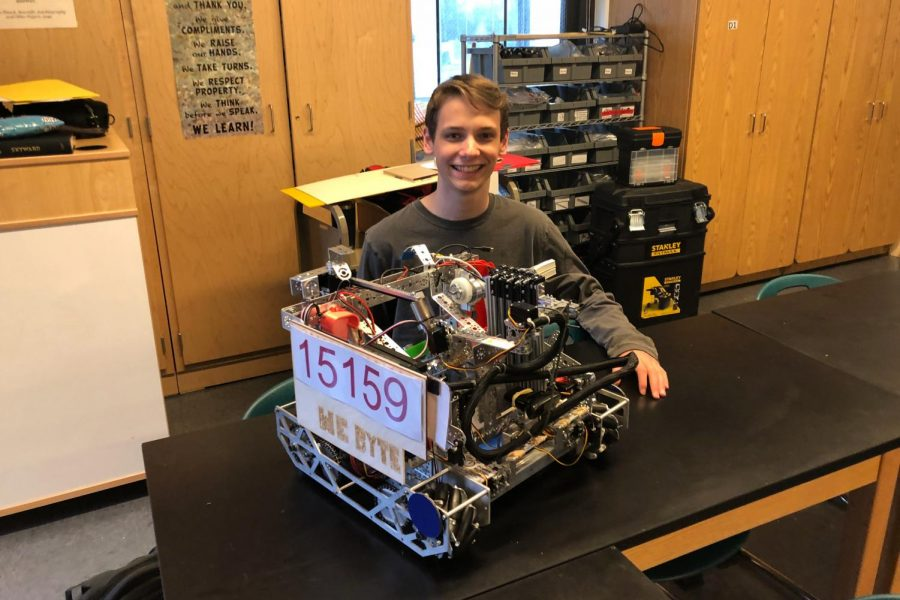 Junior Addison Goolsbee poses in robotics coach Darren Fuller's room with We Byte's robot that the team designed and built for the state competition Feb. 21. Addison was one of the robotics team members who attended the competition.