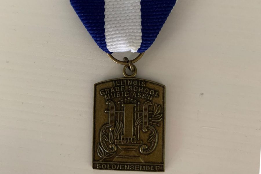 Singers who achieve a division one rating at district contest receive a medal similar to this one. Every singer from U-High achieved division one at the 2020 contest.