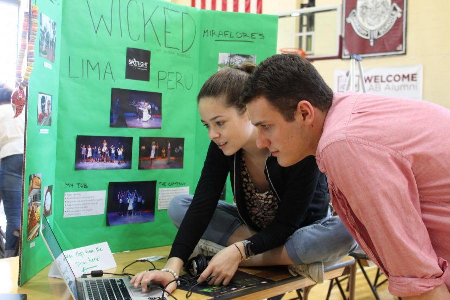Alyssa Russel, a member of the class of 2019, shows her May Project, which was to work in a production of Wicked in Peru, to fellow class member Henry Cassel at the 2019 May Project exposition. The class of 2020 will be executing their May Projects at home.