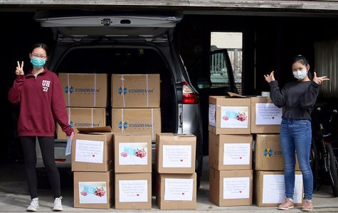 Sarina Zhao, left, and Allison Li, right, load boxes of surgical masks into their minivan for a delivery to a nursing home.