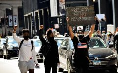 Protesters hold up signs May 30 in the Chicago Loop as they march to protest police brutality.