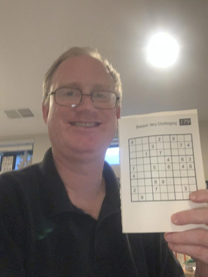 David Hartigan holds up a Sudoku puzzle. Sudoku is among is favorite acitivites.