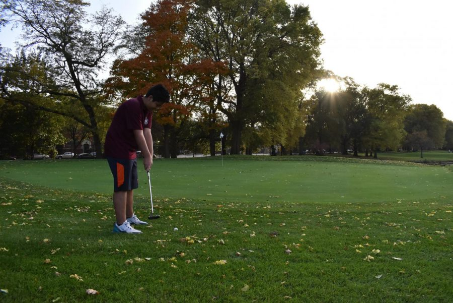 Cyrus Esmailzadeh, a golfer at U-High, steadies his golf club as he prepares to putt the ball towards the hole from outside the green in the midst of the ISL tournament.